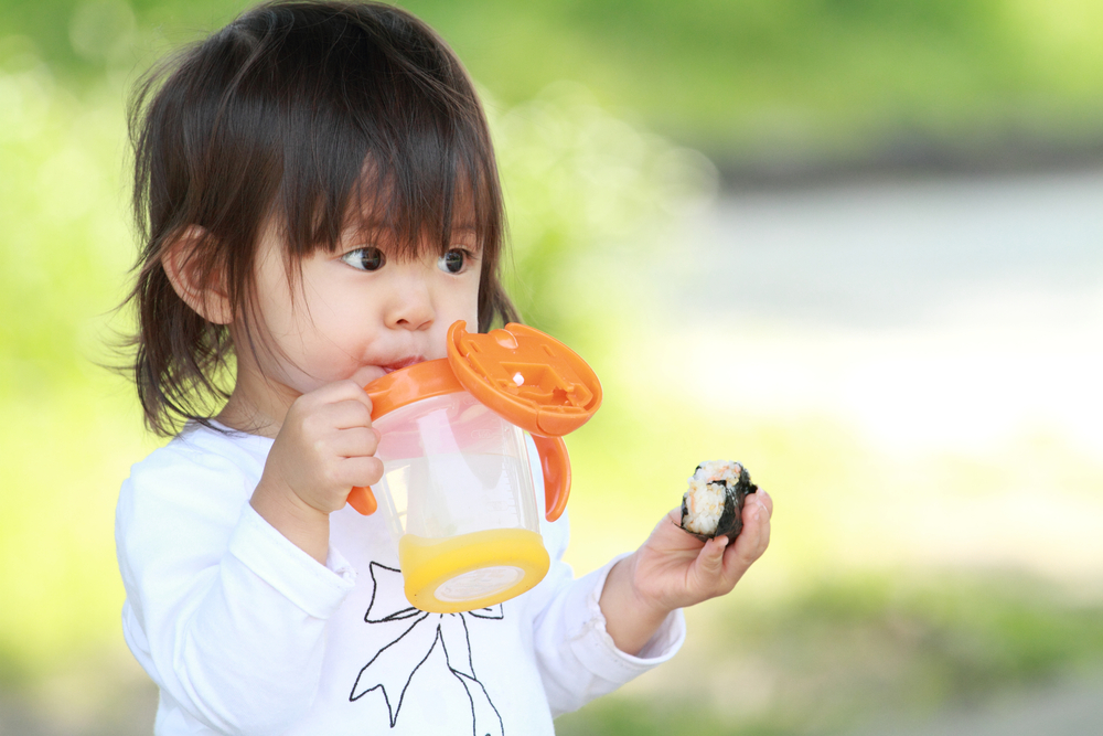 Young asian girl drinking from a sippy cup
