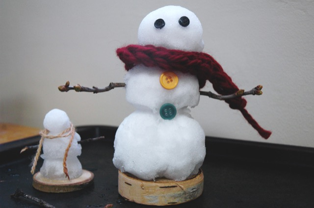 mini snow person with sticks and finger knit scarf