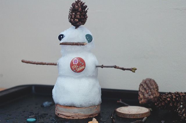 Mini snow person with sticks, buttons, spruce cones