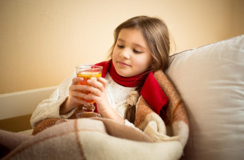 little girl drinking tea covered up with blanket
