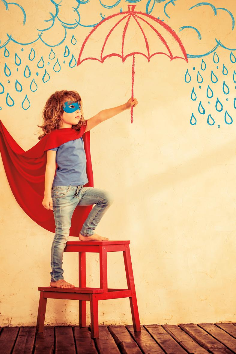 young child wearing a red cape, blue mask, and pretending to hold an umbrella painted on the wall
