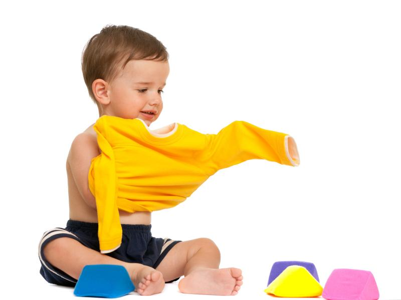 toddler putting on a yellow shirt