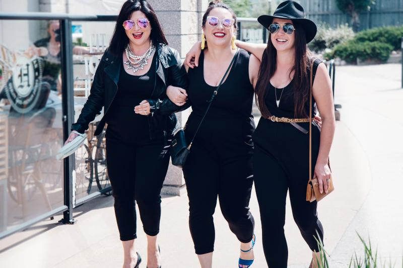 three women in black jumpsuits walking arm in arm down the street