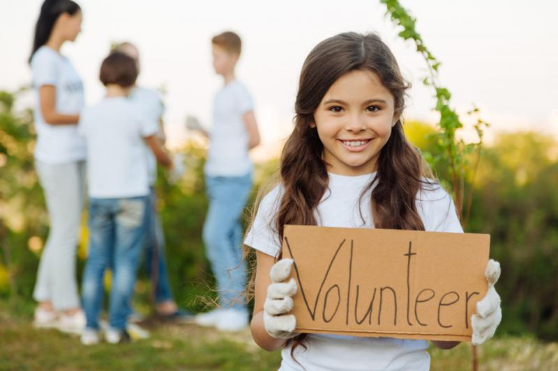 little girl holding a sign showing she is a volunteer