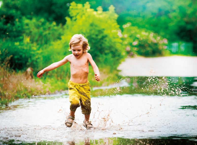 young boy running through a mud puddle