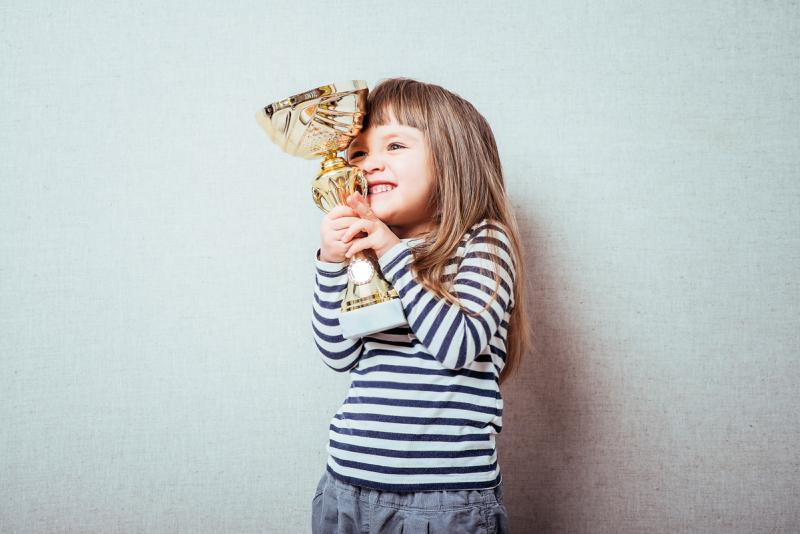 little girl hugging trophy