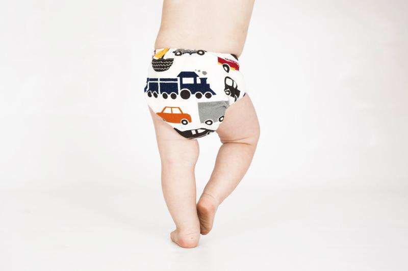 view of toddler from the middle of back down wearing cloth diaper with vehicle pattern