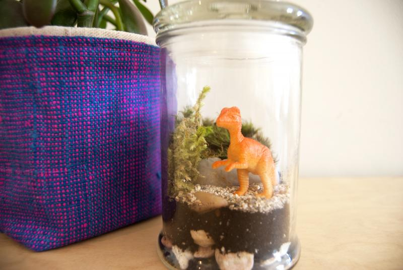 a dinosaur toy in a glass jar terrarium
