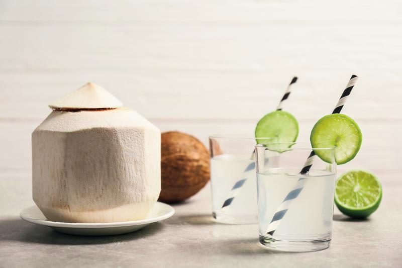 peeled coconut next to glasses of coconut water with straws