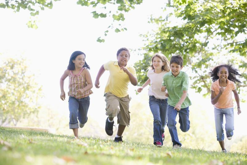 five kids running through grass toward camera