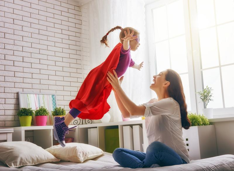 mom holding cape-wearing daughter up in the air