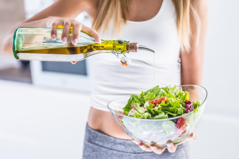 woman pouring olive oil on her salad