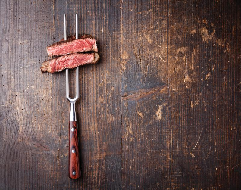 steak pierced by a meat fork on a wooden background