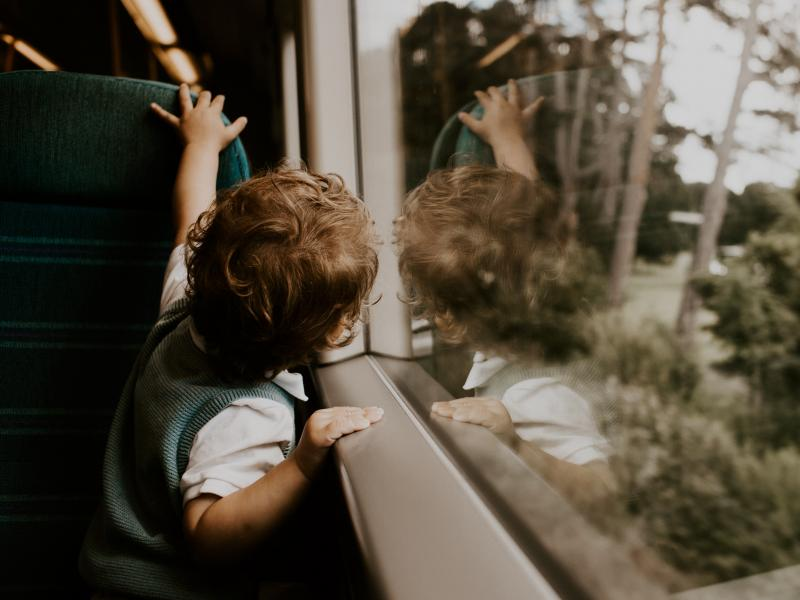small boy looking out a train window