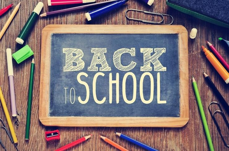 Back-to-school written on chalkboard surrounded by school supplies