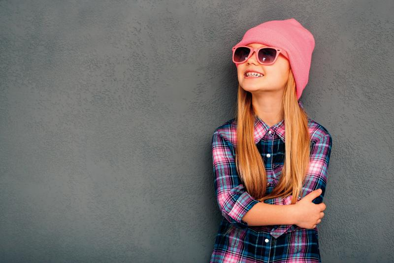 tween girl wearing a pink toque and sunglasses with a cute smile