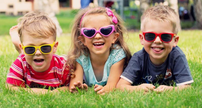 three children wearing sunglasses and lying in the grass on their bellies
