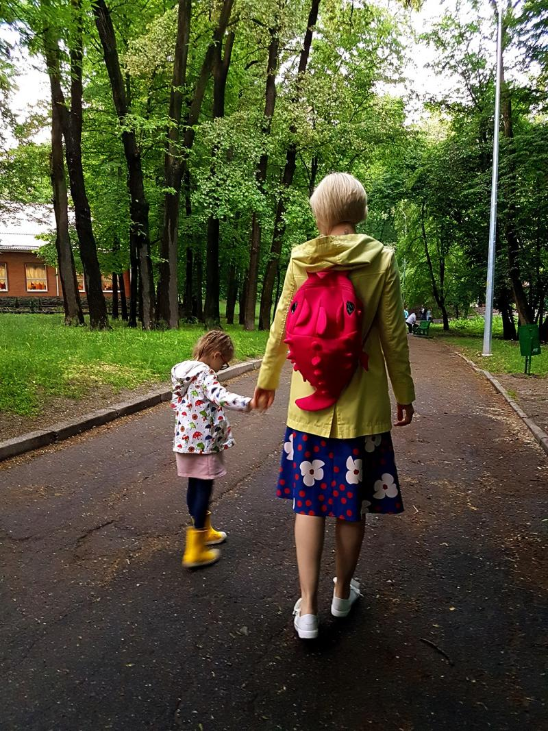 Mother and toddler walking together in a park