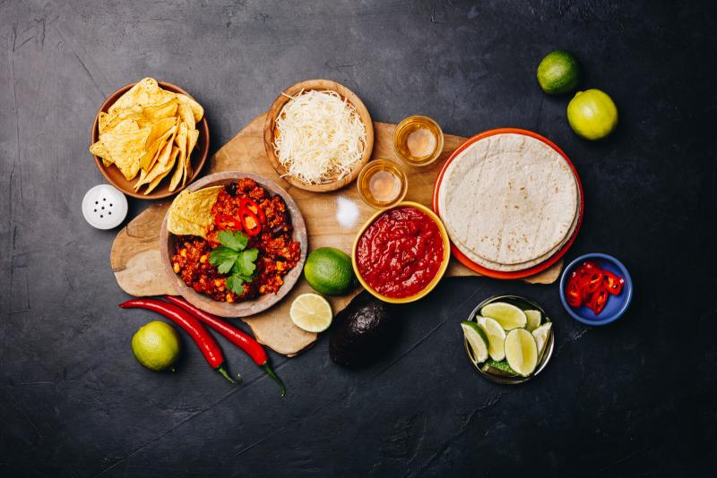 assorted taco ingredients laid out on black background