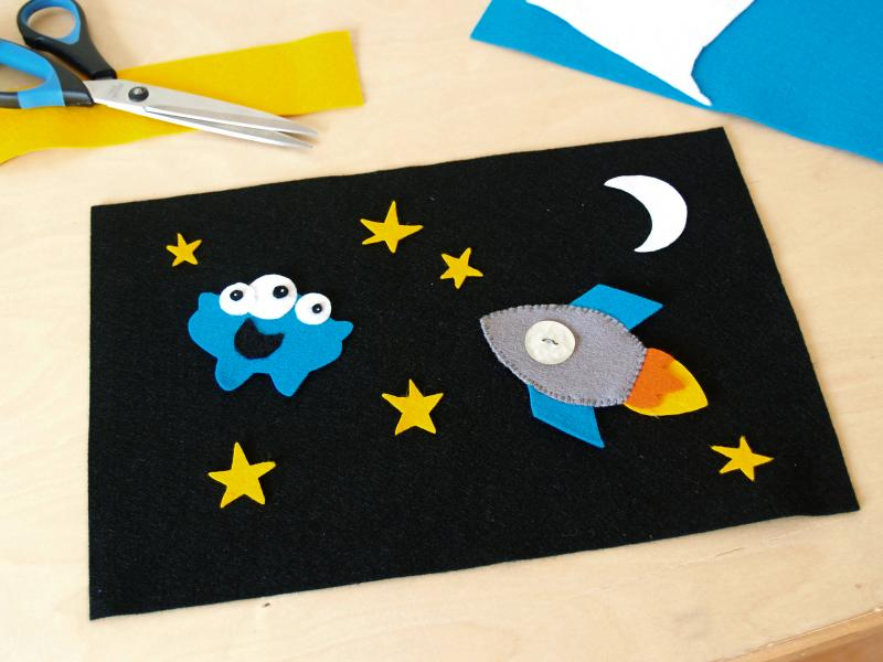 Cosmic Play Mat with rocket, stars, moon, and an alien