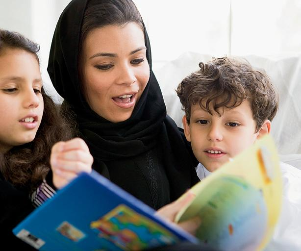 mother wearing hijab reading to children