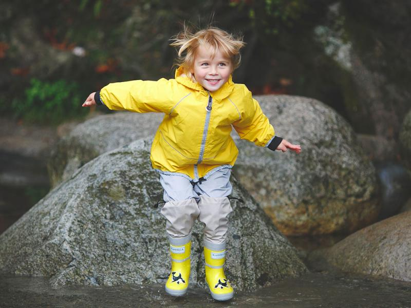 child jumping in yellow rain jacket and boots