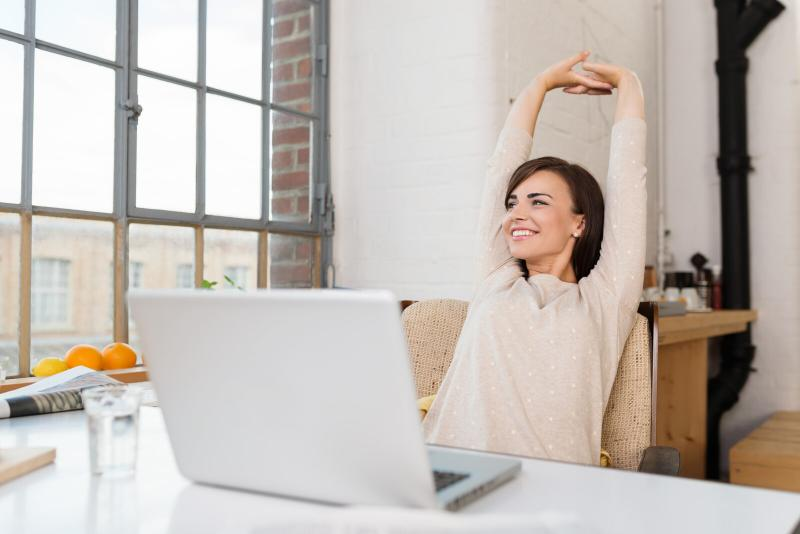woman stretching arms up in the air in front of her laptop