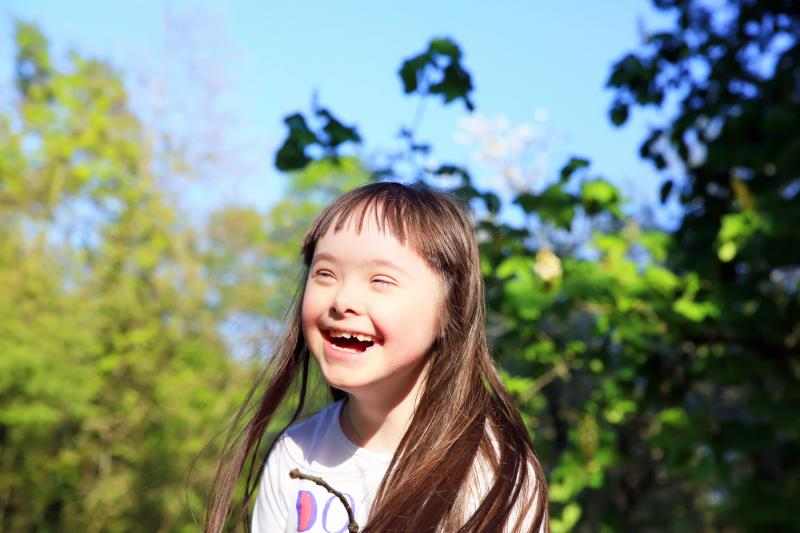 young girl laughing with trees in background