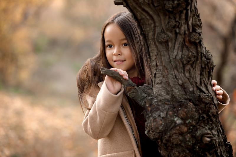 little girl peering around the trunk of a tree