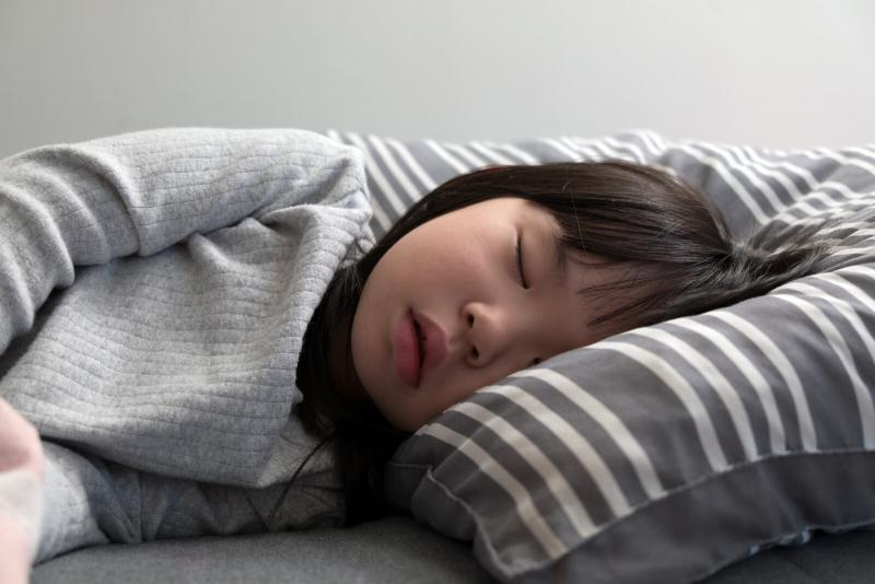 child sleeping on the bed in her bedroom