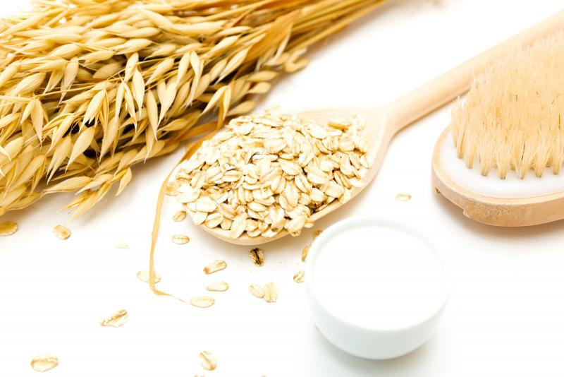 A wooden spoon holding loose oats beside a face cream and dry brush for body