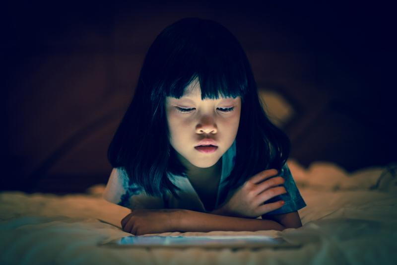 A young girl about 6 years old reads a tablet screen in an otherwise dark room