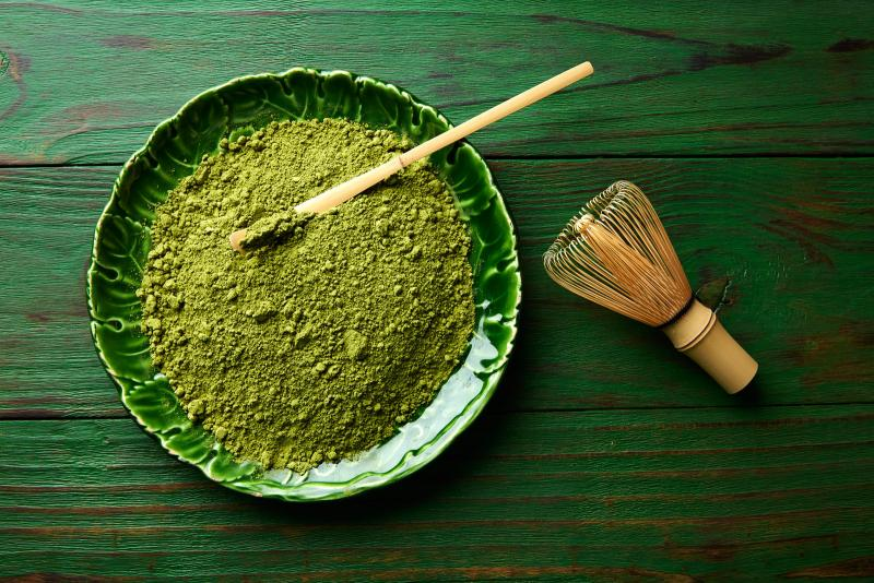 Green powdered matcha in a bowl with a whisk to the side on the table