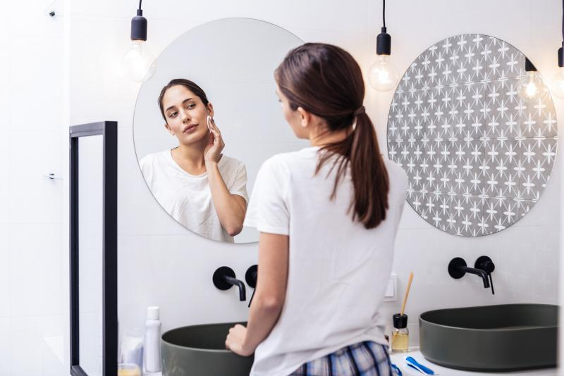 An adult woman examining her skin in the bathroom mirror.