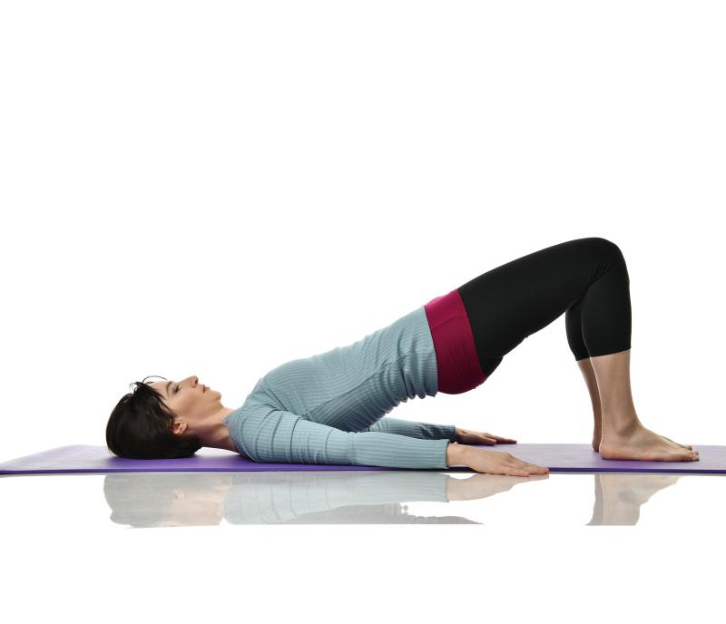 A woman in workout clothes lies on her back with her pelvis pushed up.