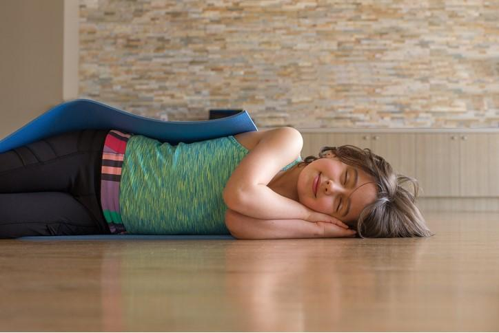 Girl sleeping happily on floor in yoga clothing