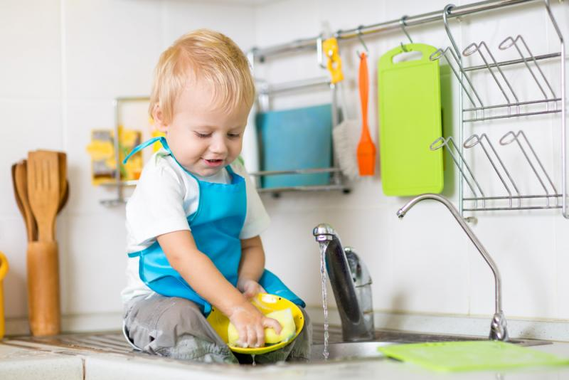Cute child washing up in kitchen sink