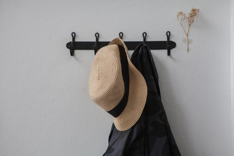 hat and coat hanging on a wall rack