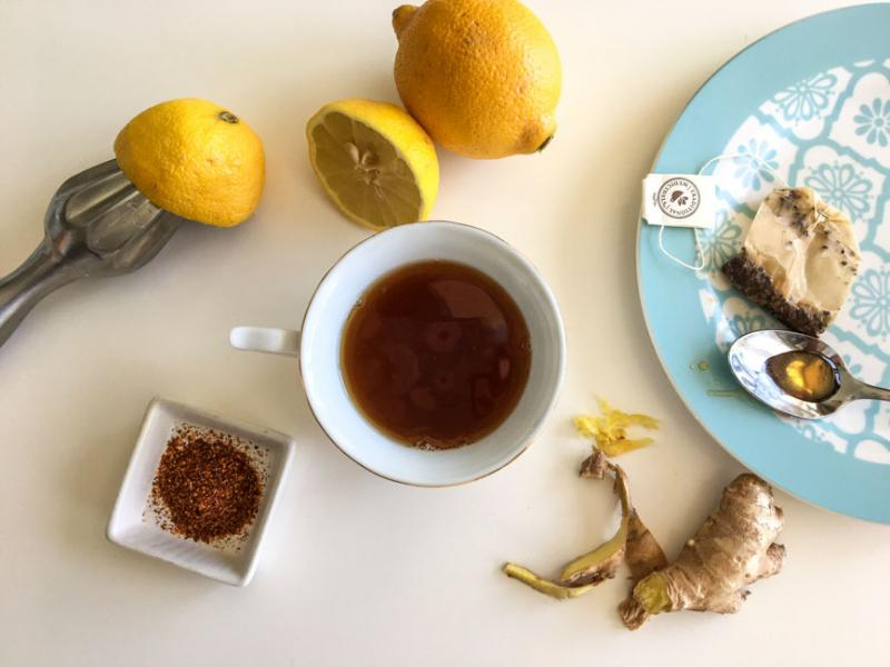 lemons, tea, ginger, spices in a bowl, tea bag and spoon on a patterned plate