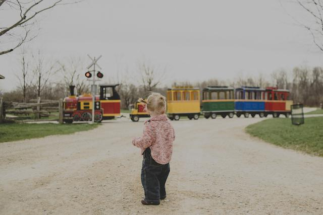 very small child looking at colourful train