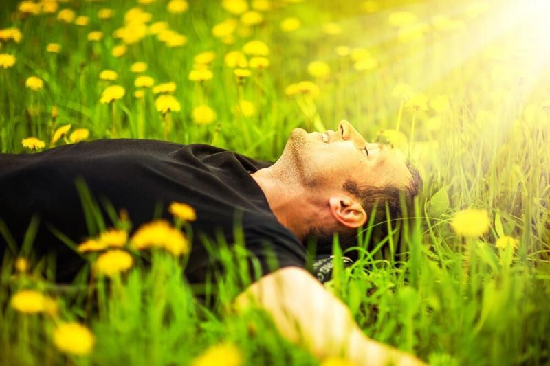 man lying happily in  green field