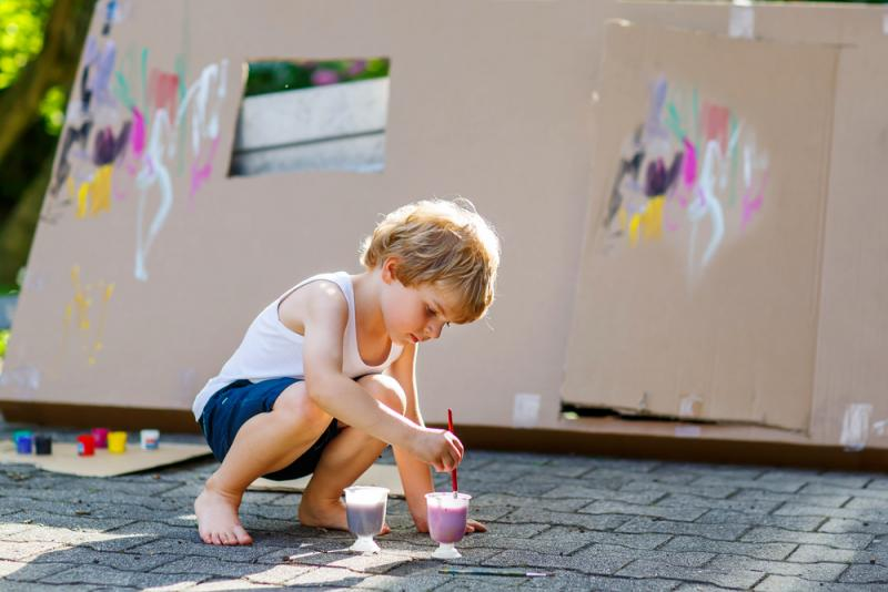school-aged boy painting cardboard in the driveway