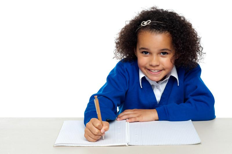 Studio shot of a cute primary kid writing her assignment