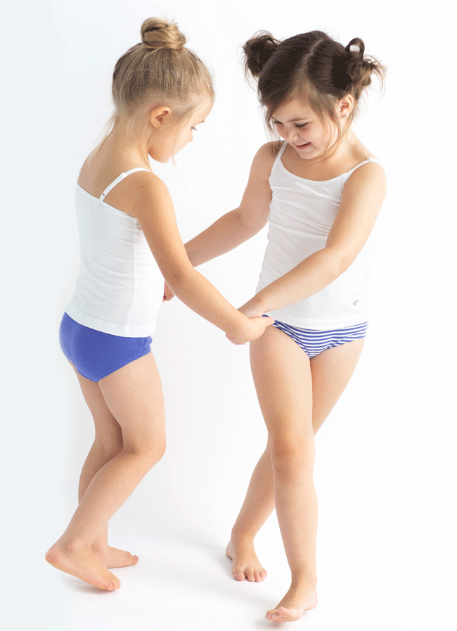 two small girls holding hands and dancing in their underwear