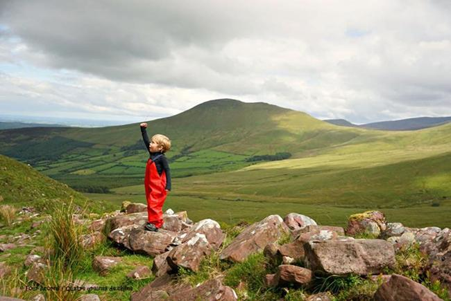 small child in red rain pants standing in mountainous surroundings
