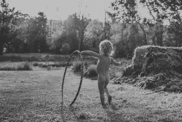 small child rolling a hula hoop