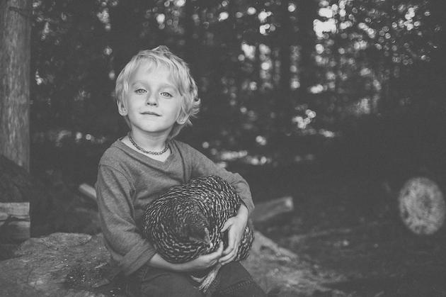 young child holding a chicken in a black and white photograph