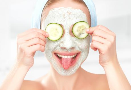 woman with facial mask holding cucumber slices on her eyes and sticking out her tongue