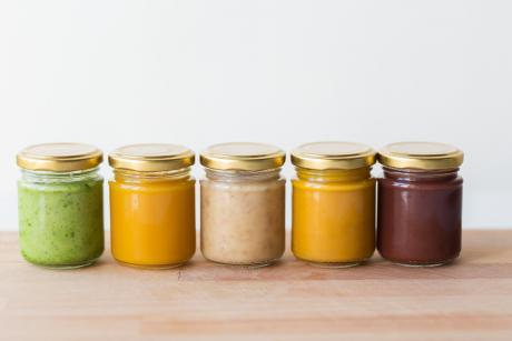row of 5 baby foods in bottles