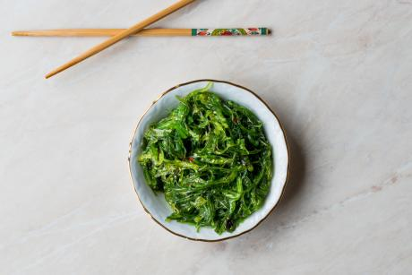 bowl of greens and chopsticks beside it